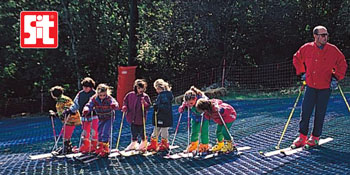 Group of children with teacher learning to ski out of season thanks to the slopes made of authentic SIT brushes