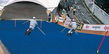 Friends skiers challenging in a slalom skiing race on a slope made of SIT brushes