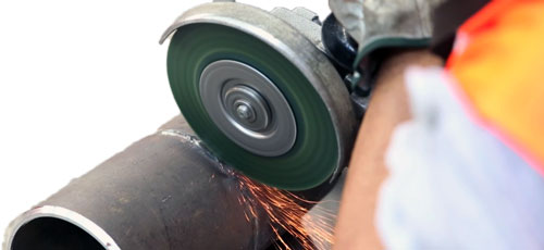 User committed to clean a welding seam with a vulcanized wheel brush